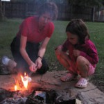 girl making smores with mother