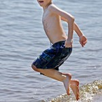child jumping into water